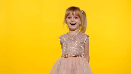 Impressed child. Perfect surprise. Exciting news. Wow reaction. Amazed astonished starting laughing young kid girl in shiny dress isolated on yellow copy space background