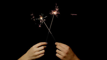 Close-up of hands or palms holding and waving burning sparklers in front of black dark background. Sparkling lights at birthday party, wedding, New Year, Christmas Eve, Xmas. 6k downscale. Bengal fire 版權商用圖片