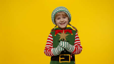 Little kid teen teenager girl 5-6 years old in Christmas elf Santa helper costume isolated on yellow studio background. Child holding star toy and making a wish. People New Year holidays celebration