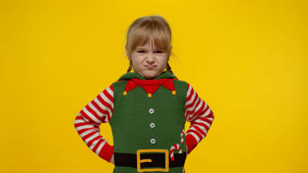 Displesed blonde kid teenager girl in elf Santa helper costume has spoiled mood on Christmas Eve isolated on yellow background. Child negative emotions, hate, rage, upset, stress. New Year holidays