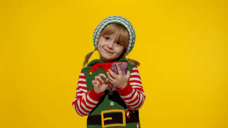 Little kid child girl in Christmas elf Santa helper costume types something on mobile phone display enjoys browsing social media sends messages of congratulations, online gifts. Yellow background