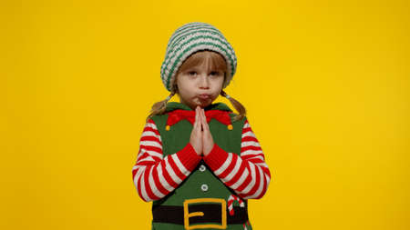 Child girl pleads about gifts on New Year. Pleading kid in Christmas elf Santa helper costume begs, prays for forgiveness feels sorry and guilty, keeps palms together, standing over yellow background