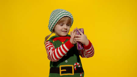 Joyful kid child girl in Christmas elf Santa helper costume making a video call on mobile phone to Santa Claus, making a wish, online internet gifts. Yellow background. New Year holidays
