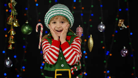 Impressed child kid girl in Christmas elf Santa Claus helper costume looks at camera makes big eyes covering mouth with hands feel horrified isolated on black background. OMG, wow, stunned, shocked