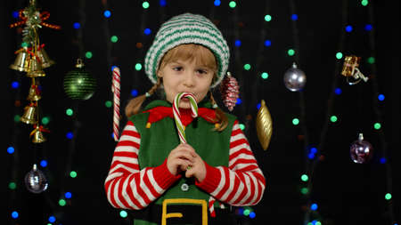 Child enjoying caramel sweets. Blonde kid girl in Christmas elf Santa Claus helper costume licking candy cane lollipop isolated on black background with garland. People New Year holidays celebration