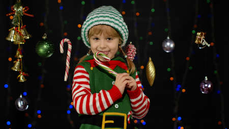 People New Year holidays celebration. Blonde kid girl in Christmas elf Santa Claus helper costume licking candy cane lollipop isolated on black background with garland. Child enjoying caramel sweets 版權商用圖片