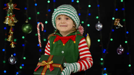 Kid child in Christmas elf Santa Claus helper costume holding present surprise red gift box with ribbon isolated on black background. People New Year holidays celebration