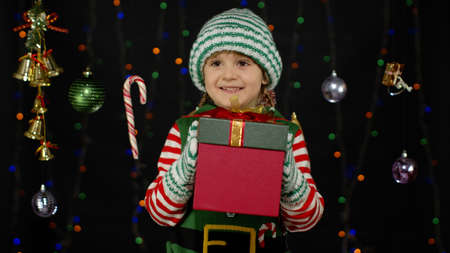 Kid child in Christmas elf Santa Claus helper costume holding present surprise red gift box with red ribbon isolated on black background. People New Year holidays celebration