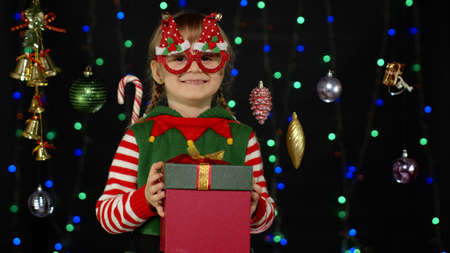 Lovely teen kid girl in Christmas elf Santa helper costume isolated on black background with garland. Child giving present gift box to camera, smiling sweetly. People New Year holidays celebration 版權商用圖片
