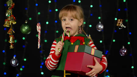 Kid girl in Christmas elf Santa Claus helper costume licking candy cane lollipop on black background with garland. Child with surprise gift box enjoying caramel sweets. New Year holidays celebration