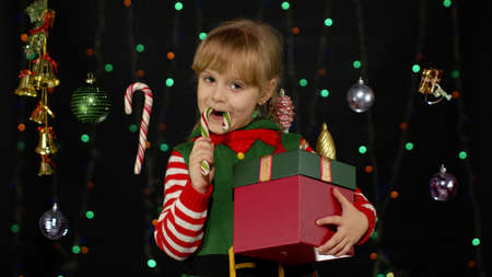 Child with surprise gift box enjoying caramel sweets. Kid girl in Christmas elf Santa Claus helper costume licking candy cane lollipop on black background with garland. New Year holidays celebration