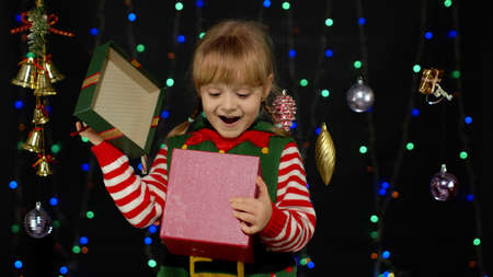 Teen kid girl in Christmas elf Santa helper costume on black background. Child with present gift box, expressing amazement, extreme happiness looking, opening inside box. New Year holidays celebration 版權商用圖片