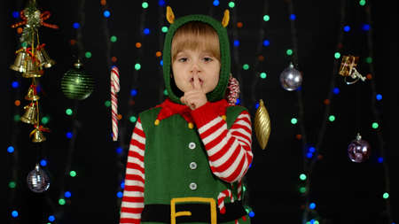 Kid girl in Christmas elf Santa Claus helper costume looking around and holding finger near lips for silence isolated on black background. Child showing hush sign at gesturing. New Year holidays