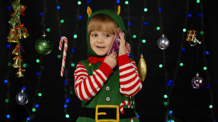 Joyful kid child girl in Christmas elf Santa helper costume making call on mobile phone to Santa Claus or sends messages of congratulations, online gifts. Black background. New Year holidays