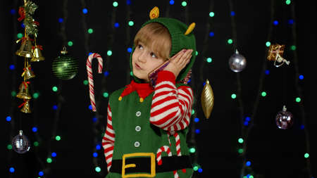 Joyful kid child girl in Christmas elf Santa helper costume making call on mobile phone to friends or mother, sends messages of congratulations, online gifts. Black background. New Year holidays 版權商用圖片