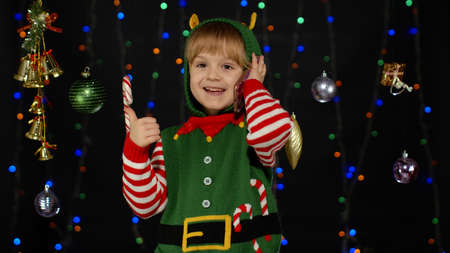 Joyful kid child girl in Christmas elf Santa helper costume making online call on mobile phone to Santa Claus, asking for a lot of gifts. Black background. New Year holidays. 6k downscale, slow motion 版權商用圖片