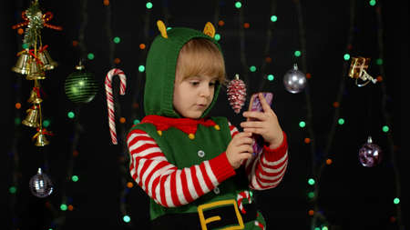 Little kid child girl in Christmas elf Santa helper costume types something on mobile phone display enjoys browsing social media sends messages of congratulations, online gifts. Black background