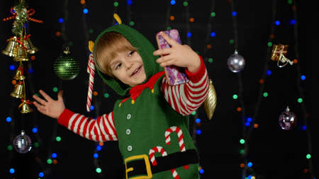 Kid girl in Christmas elf Santa Claus helper costume making selfie on smartphone near festive decorations toys isolated on black background with garland. Child using mobile phone. New Year holidays