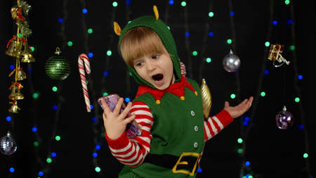 Joyful kid child girl in Christmas elf Santa helper costume making a video call on mobile phone to Santa Claus or sends messages of congratulations, online gifts. Black background. New Year holidays 版權商用圖片