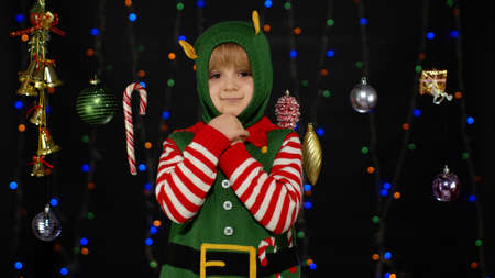 Little blonde kid teen teenager girl in Christmas elf Santa helper costume posing isolated on black background. Child dancing, fooling around, making funny faces. People New Year holidays celebration
