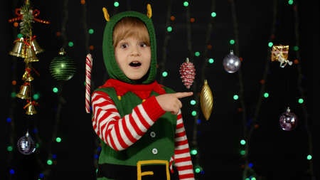 Teen kid girl in Christmas elf Santa Claus helper costume pointing at something and showing thumbs up gesture, agree sign isolated on black background. Child smiling. New Year holidays celebration 版權商用圖片