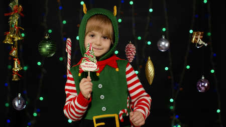 Blonde kid girl in Christmas elf Santa Claus helper costume with candy lollipop sweets isolated on black background with garland. Child enjoying caramel sweets. People New Year holidays celebration