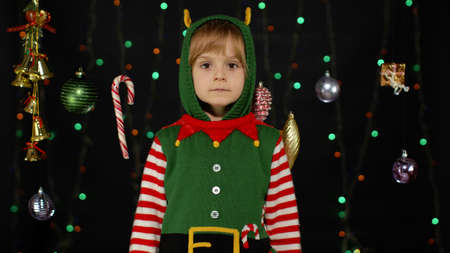 Shy shamed child girl in Christmas elf Santa helper costume posing and making funny faces. Kid feels guilty. Isolated on black background with garland. People emotions. New Year holidays celebration 版權商用圖片