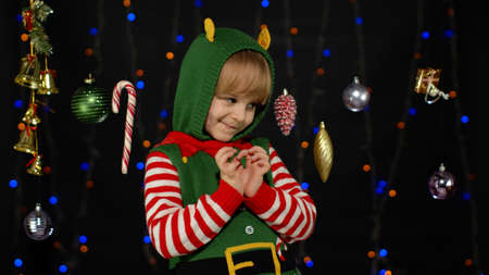Sly kid teen girl steepls fingers and schemes something gets interesting idea how to decorate house, waiting for gift box. New Year and Christmas holidays winter time. Child Christmas elf Santa helper