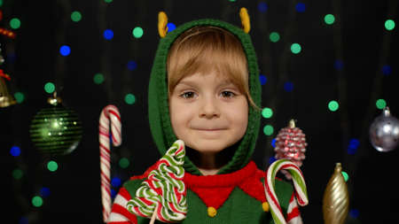 Blonde kid girl in Christmas elf Santa Claus helper costume with lollipop candy cane sweets isolated on black background with garland. Child enjoying caramel sweets. New Year holidays celebration