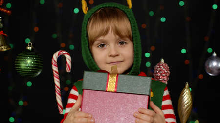 Child giving present gift box to camera, smiling sweetly. Lovely teen kid girl in Christmas elf Santa helper costume isolated on black background with garland. People New Year holidays celebration