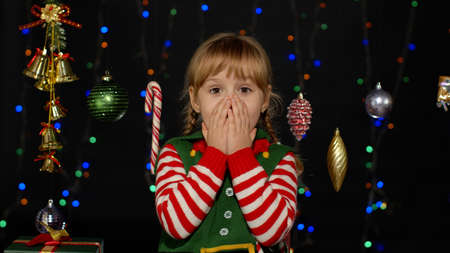 Impressed child kid girl in Christmas elf Santa Claus helper costume looks at camera makes big eyes covering mouth with hands feel horrified isolated on black background. OMG, wow, stunned, shocked 版權商用圖片