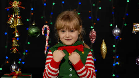 Shy shamed child girl in Christmas elf Santa helper costume posing and making funny faces. Yes gesture. Isolated on black background with garland. People emotions. New Year holidays celebration