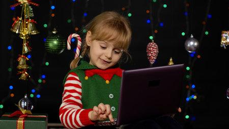 Kid girl in Christmas elf Santa Claus helper costume doing shopping online using laptop isolated on coronavirus quarantine lockdown. Child having video chat browsing on social media. New Year holidays