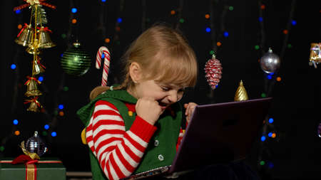 Child looking for presents, gift for friends and family, doing shopping online using mobile phone isolated on coronavirus quarantine lockdown. Kid girl in Christmas elf Santa Claus helper costume
