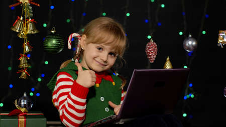 Child looking for presents, gift for friends and family, doing shopping online using laptop isolated on coronavirus quarantine lockdown. Kid girl in Christmas elf Santa Claus helper costume. New Year