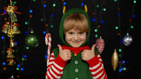 Teen kid girl in Christmas elf Santa Claus helper costume showing thumbs up gesture, agree sign isolated on black background with garland decorations toys. Child smiling. New Year holidays celebration