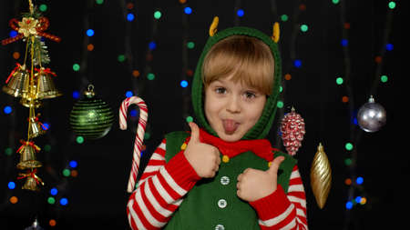 Teen kid girl in Christmas elf Santa Claus helper costume showing thumbs up gesture, agree sign on black background with garland decorations toys. Child smiling, showing tongue. New Year holidays 版權商用圖片
