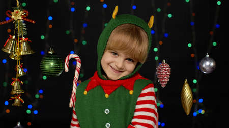 Shy shamed child girl in Christmas elf Santa helper costume posing and smiling. Kid feels guilty. Isolated on black background with garland. People emotions. New Year holidays celebration