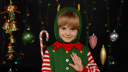 Teen kid girl 5-6 years old in Christmas elf Santa helper costume waving greeting with hand as notices someone. Hello, hi, greetings gesture. Small child smiling. People New Year holidays celebration