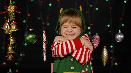 Little fun blonde kid teen teenager girl in Christmas elf Santa helper costume hugging, embracing. Joyful child smiling, flirting. People New Year holidays celebration 版權商用圖片