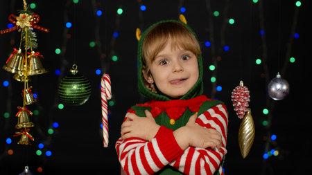 Little fun blonde kid teen teenager girl in Christmas elf Santa helper costume hugging, embracing, showing tongue. Joyful child smiling, flirting. People New Year holidays celebration 版權商用圖片
