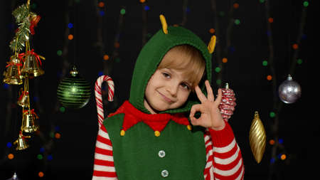Blonde teen kid girl in Christmas elf Santa Claus helper costume showing okay sign isolated on black background with garland. Child smiles to camera with ok gesture. New Year holidays celebration