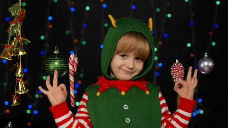 Child smiles to camera with ok gesture. Blonde teen kid girl in Christmas elf Santa Claus helper costume showing okay sign isolated on black background with garland. New Year holidays celebration