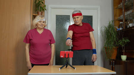 Senior elderly couple man and woman exercising. Old grandmother grandfather doing healthy lifestyle workout, training, fitness, sport activity at home. Trainers shoots video blog trainings online vlog 版權商用圖片
