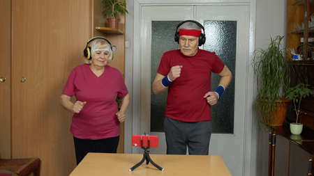Senior elderly joggers couple man and woman watching online workout exercises on mobile phone and training, running together at home. Mature grandmother and grandfather during coronavirus lockdown