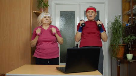 Retired senior couple man woman doing workout with dumbbells, training, fitness, sport activity exercises at home. Elderly grandmother grandfather starting stream, vlog, blog, online distance course