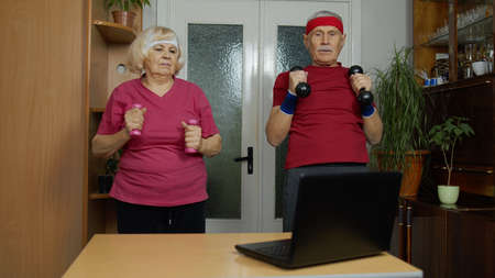 Mature couple man and woman fitness trainer coach records video online dumbbells workout course with laptop live streaming sport exercises at home. Senior grandmother and grandfather live stream, blog