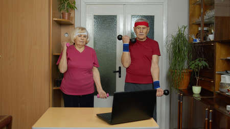 Senior elderly couple man woman watching online workout exercises on laptop and training with dumbbells together at home. Mature old grandmother and grandfather during coronavirus pandemic lockdown