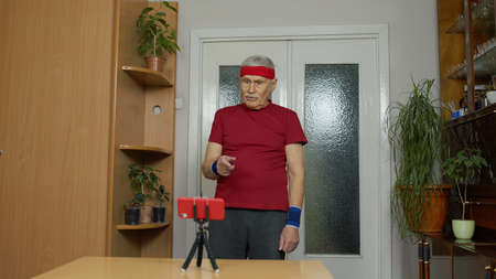 Senior elderly man exercising. Old grandfather doing workout, training, fitness, sport activity at home. Trainer shoots video blog trainings online vlog course during coronavirus