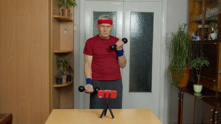 Senior elderly man watching online distance workout exercises with dumbbells on mobile phone and training, fitness, sport activity at home. Mature grandfather during coronavirus lockdown quarantine 版權商用圖片